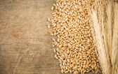 Ears spike and wheat on wood texture — Stock Photo