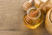 Glass jar full of honey and stick — Stock Photo