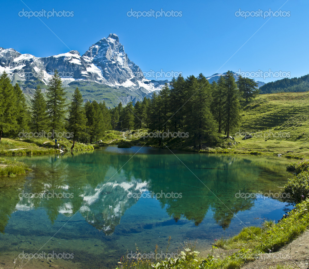 The Matterhorn reflected in the clear waters of blue lake, Valtournenche - Aosta Valley — Stock Photo #10541101