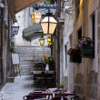 Narrow street with flowers, restaurant, lamps,and stairs — Stock Photo #10704913