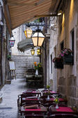 Narrow street with flowers, restaurant, lamps,and stairs — Stock Photo