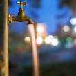 Long exposure night shot of flowing water from old rusty tap — Stock Photo #10681558
