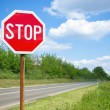 Stop sign by the empty road — Stock Photo
