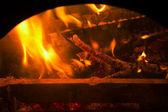 Burning billets in old fireplace — Stockfoto