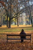 Lonely girl sitting in the autumn park — Stock Photo