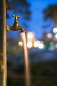 Long exposure night shot of flowing water from old rusty tap — Stock Photo