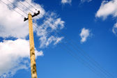 Retro telephone pole over cloudy sky — Stock Photo