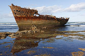 Rusty shipwreck on the coast. — Stock Photo