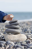 Childs hand putting white pebble on the top of the tower. — Stock Photo