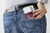 Woman taking Czech Passport and money out of jeans pocket — Stock Photo