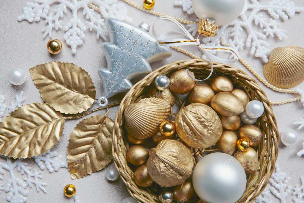 Golden nuts, shell, beads and white ball lying in the basket on the christmas backdrop — Stock Photo #10709217