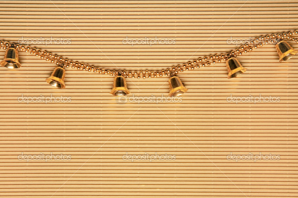 Golden bells with beads over yellow background — Stock Photo #10709222