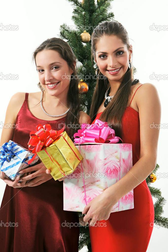 Two young beautiful woman in red dress are holding the presents near christmas tree  Stock Photo #10709288
