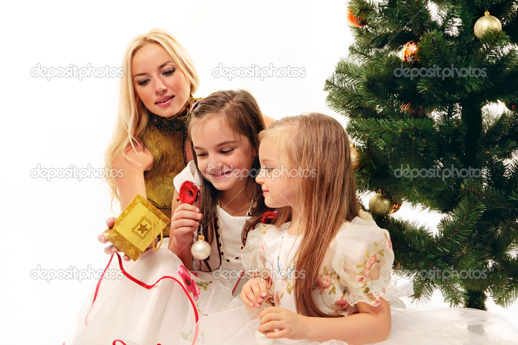 Beautiful mother makes a present to her children in christmas — Stock Photo #10709295