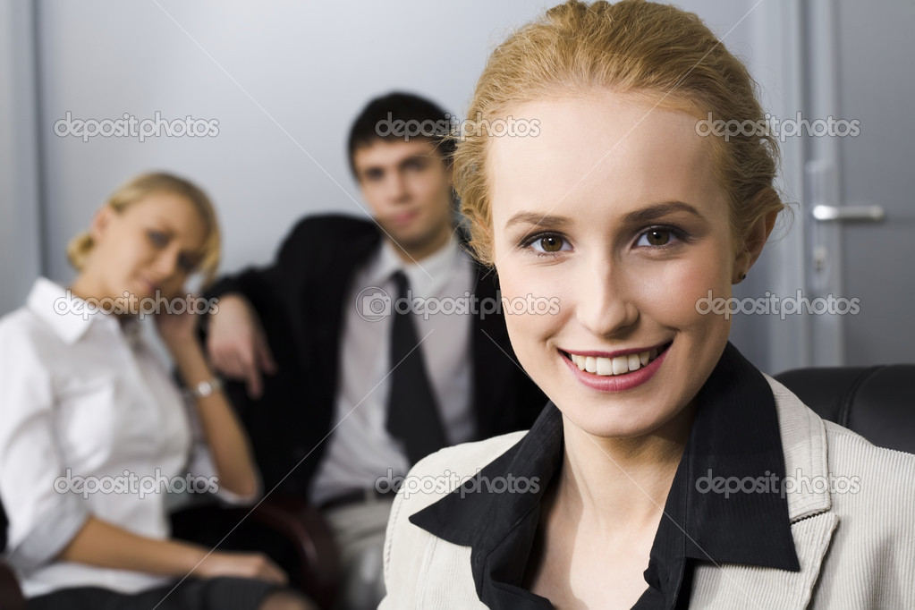 Portrait of smiling businesswoman and two her partners on the background — Stock Photo #10709341