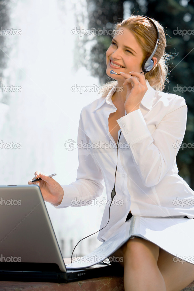 Portrait of friendly smiling customer support operator sitting near the fountain  Stock Photo #10709361