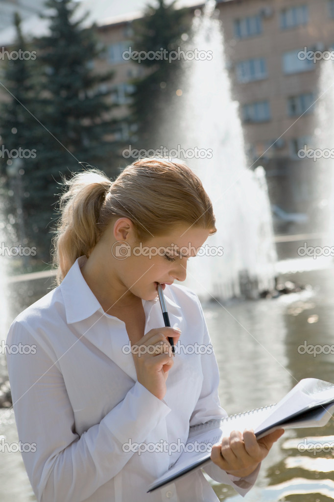 Portrait of pretty business woman reading an interesting agreement in the park  Stock Photo #10709364