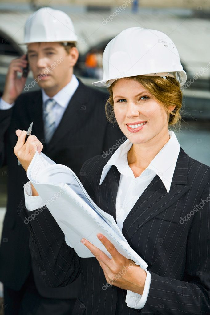Businesswomen is holding architectural plan and pen on the background of her co-worker — Stock Photo #10709395