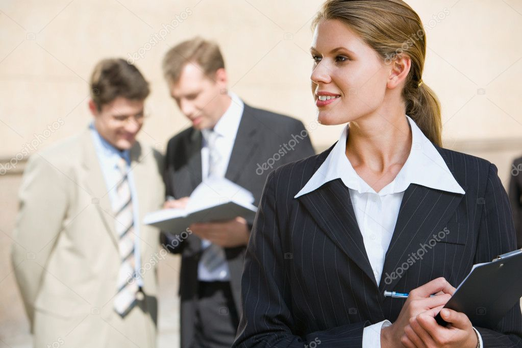 Successful young woman is writing a text on the background of two businesspeople — Stock Photo #10709406