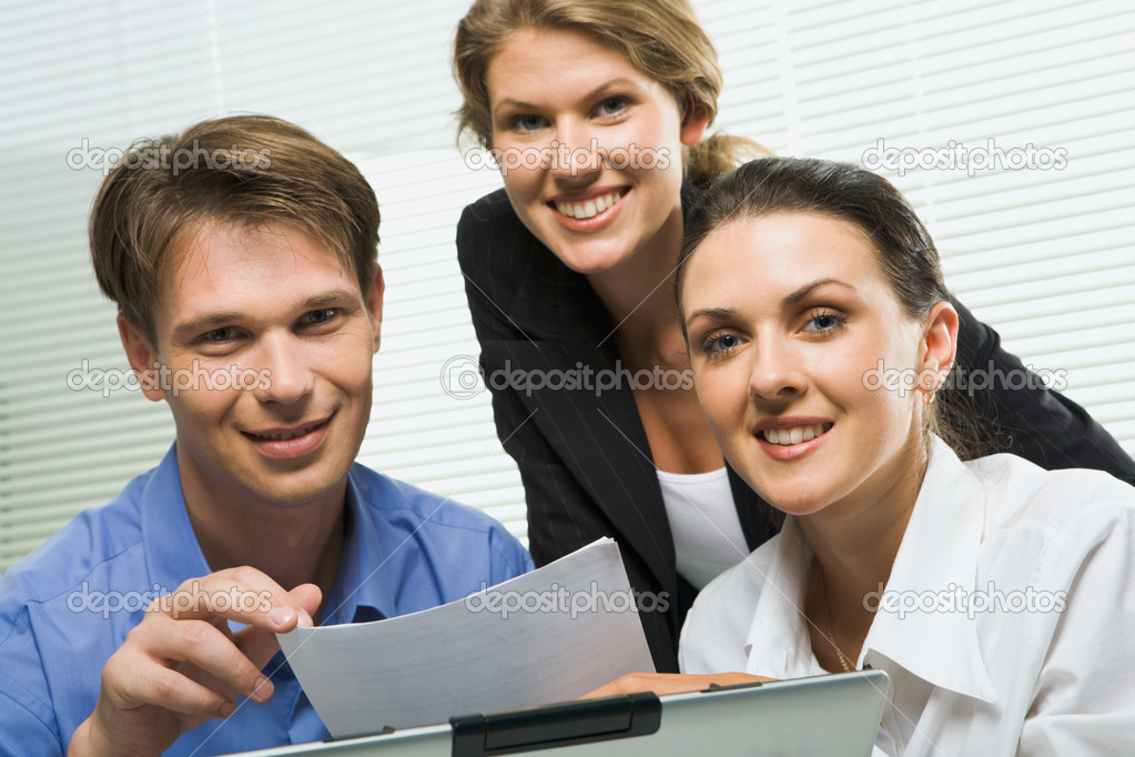 Portrait of three business looking at camera in a working environment  Stock Photo #10709475