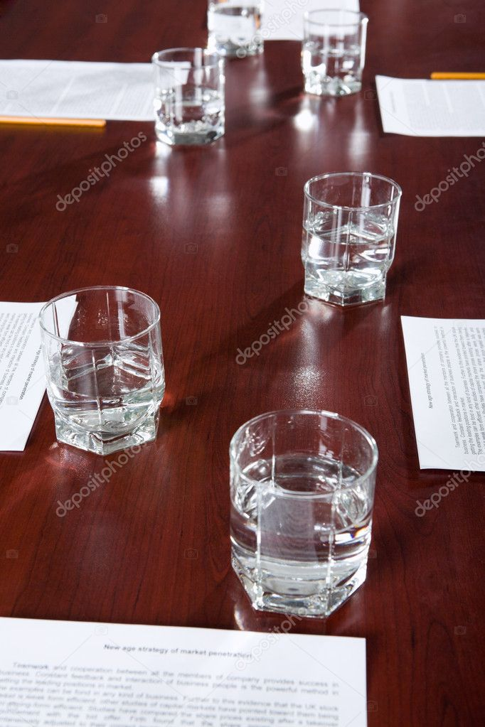 Ordinary workplace: papers with pencils and glasses of water on a table  Stock Photo #10709931