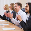 Business sitting in a row and applauding — Stock Photo