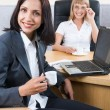 Portrait of happy young businesswomen looking at camera in office — Stock Photo