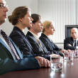Stock Photo: Tense young are sitting at table in line and their displeased boss