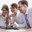 Group of three business looking at monitor — Foto de Stock