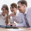Group of three business looking at monitor — Stockfoto
