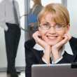 Young attractive office worker is looking at camera touching the laptop on the background of her colleagues — Stock Photo