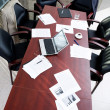Empty boardroom: black chairs around table with business objects on it — Stock Photo