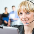 Portrait of friendly smiling telephone operator in a working environment — Stock Photo
