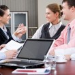Image of laptop on workplace with associates talking on background — Stock Photo #10710981