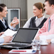 Image of laptop on workplace with associates talking on background — Stock Photo