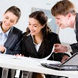 Image of three happy business looking at business plan with smiles — Stock Photo