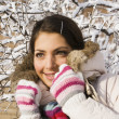 Smiling positive girl among winter twigs - Stock Photo