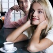 Stock Photo: Smiling cute blond womdrinking coffee in bar