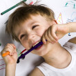 Laughing boy lying on his drawing with felt-tip pen in his teeth — Stockfoto