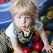 Stock Photo: Lad seated on colorful balls and looking at camera
