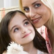 Royalty-Free Stock Photo: Smiling beautiful blond mother caring for her daughter holding her beloved bear