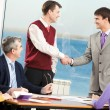 Successful partners shaking hands while their colleagues looking at them — Stock Photo #10718378