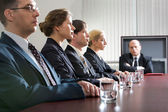 Tense young are sitting at the table in a line and their displeased boss — Stockfoto