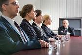 Gespannen jonge zitten aan de tafel in een lijn en hun ontevreden baas — Stockfoto
