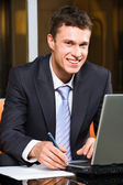 Photo of confident manger sitting at the table with laptop and document — Stock Photo