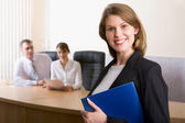 Portrait of happy businesswoman smiling at camera on background of working — Stock Photo