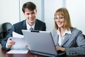 Image of two working looking at laptop screen in office — Stock Photo