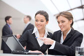 Portrait of two smiling business women working together — Stock Photo
