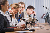 Four successful young sitting in a line in front of monitors speaking on microphones — Stock Photo