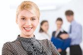 Porträtt av blond affärskvinna tittar på kameran i arbetsmiljön — Stockfoto